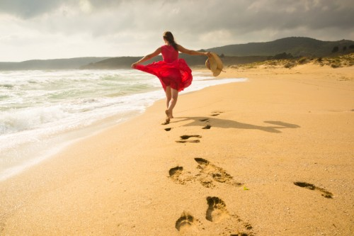 Beautiful happy woman running freely on the beach